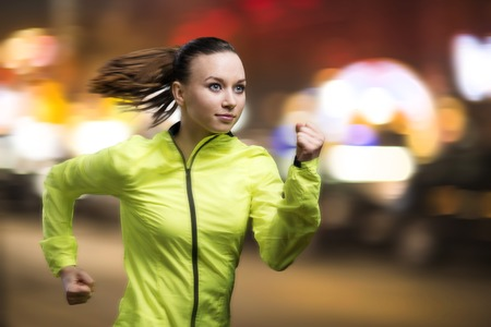 night shirt: Young woman jogging at night in the city Stock Photo