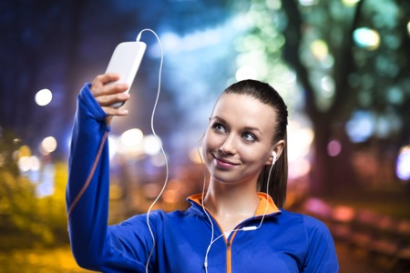 Young woman jogging at night in the city taking selfie photo