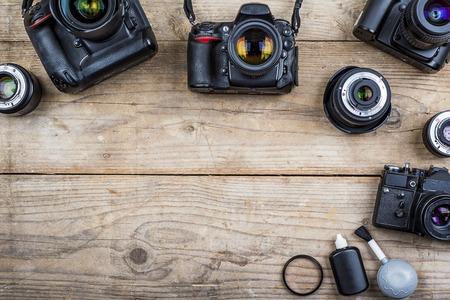 old desk: Mix of old cameras on wooden desk background. Stock Photo
