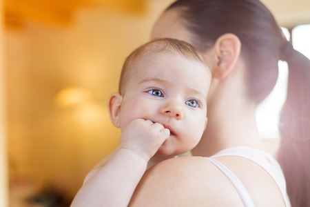 adult baby: Cute little baby in the arms of her mother in a living room.