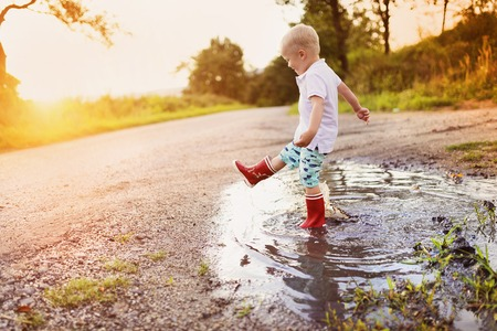 sunglight: Little boy playing outside in a puddle Stock Photo