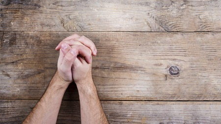 Hands of praying young man on a wooden desk background.