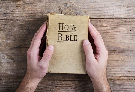bible ouverte: Mains tenant la Bible sur un bureau fond en bois.