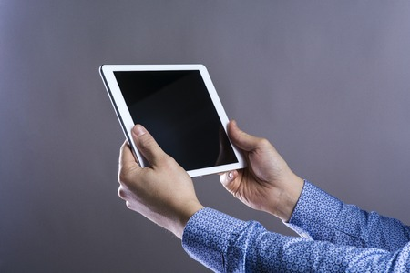 Unrecognizable young hipster with his tablet. Studio shot on gray background. photo