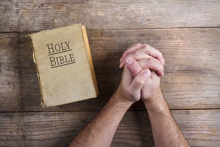 biblia: Manos de rogaci�n joven y Biblia sobre un fondo de escritorio de madera.