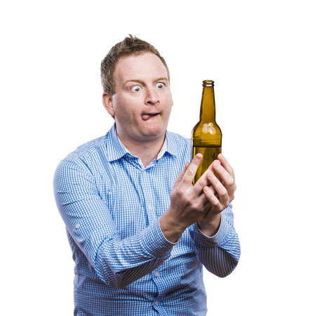 intoxicated: Funny young drunk man holding a beer bottle. Studio shot on white background.