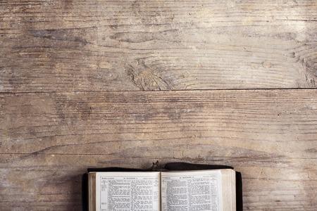 libro abierto: Biblia abierta sobre un fondo de escritorio de madera. Foto de archivo