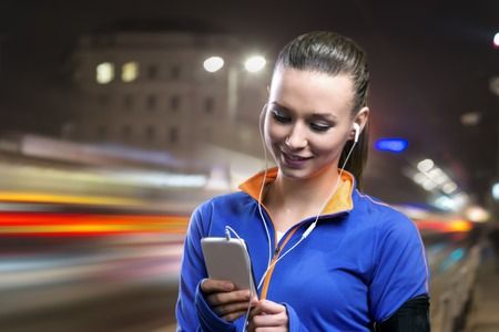 night shirt: Young woman jogging at night in the city while listening music Stock Photo