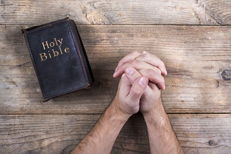 church: Hands of praying young man and Bible on a wooden desk background.