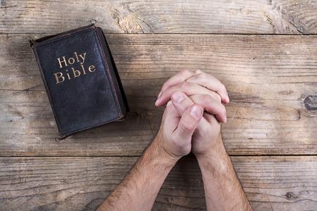 iglesia: Manos de rogaci�n joven y Biblia sobre un fondo de escritorio de madera.