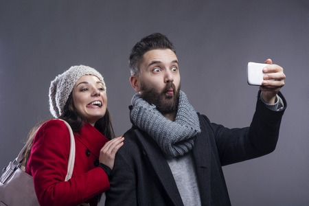 Trendy young hipster couple with coffee and smart phone. Studio shot on gray background. photo