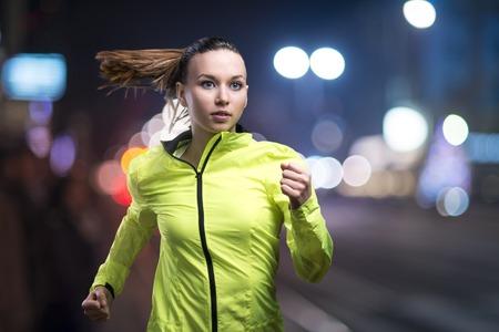 都市の夜ジョギングする若い女性