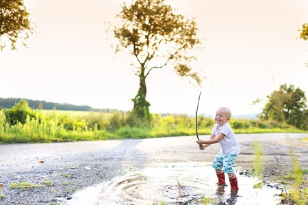 enjoy life: Little boy playing outside in a puddle Stock Photo