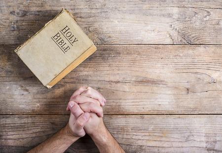 木製の机の背景に若い男と聖書の祈りの手。