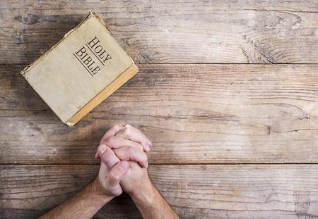 Hands of praying young man and Bible on a wooden desk background.