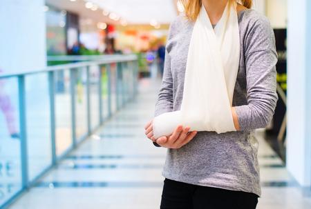 Mooie vrouw met een gebroken arm binnenkant van een winkelcentrum Stockfoto