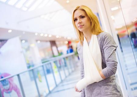 ショッピング センターの中の腕の骨折と美しい女性