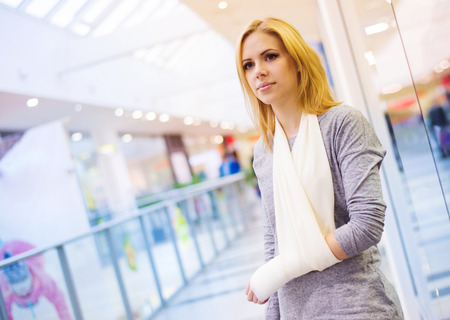 injure: Beautiful woman with broken arm inside of a shopping center