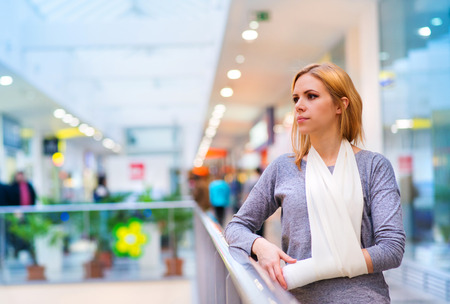Beautiful woman with broken arm inside of a shopping center