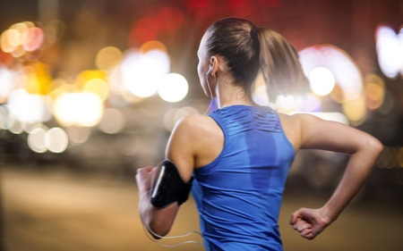 jog: Young woman jogging at night in the city Stock Photo