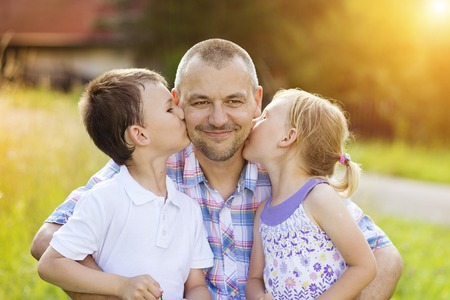 Father with his two children spending time together outside in green nature. Stock Photo