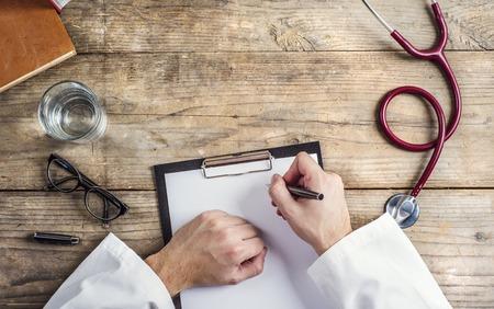 persona escribiendo: Manos de irreconocible m�dico escrito en una hoja de papel en blanco. Fondo de escritorio de madera. Foto de archivo