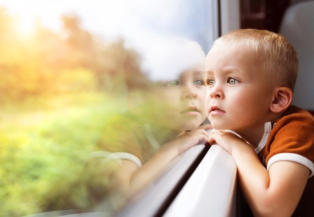young boy: Little boy traveling in train looking outside the window. Stock Photo