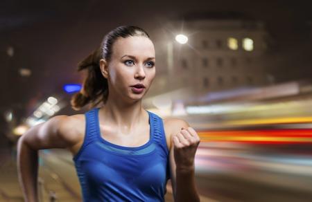 若い女性の都市の夜のジョギング