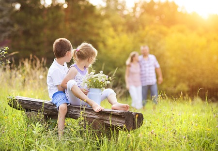 outdoor bench: Happy young family spending time together outside in green nature. Stock Photo
