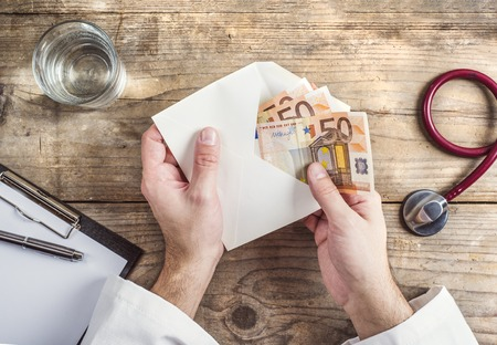 bribe: Hands of unrecognizable doctor accepting a bribe. Wooden desk background. Stock Photo