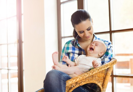 Crying little baby in the arms of her mother in a living room. photo