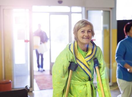 pierna rota: Mujer mayor heridos que caminar por el pasillo del hospital con muletas Foto de archivo