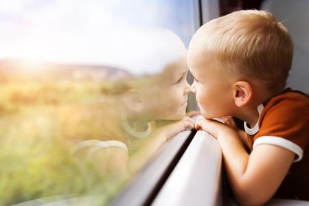Little boy traveling in train looking outside the window. Standard-Bild