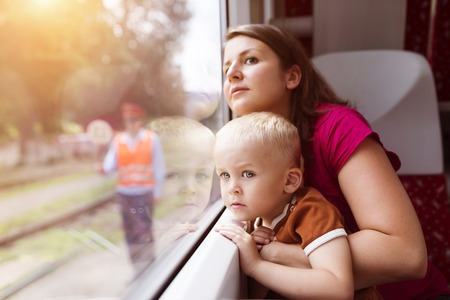 vehicle window: Mother with son in her lap traveling in train.