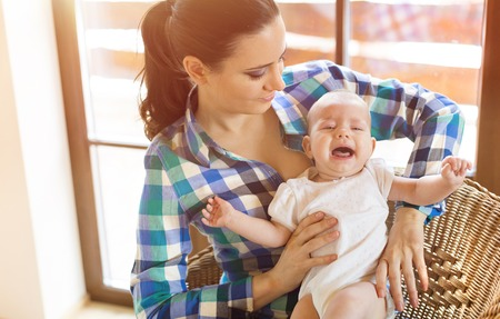 adult crying: Crying little baby in the arms of her mother in a living room. Stock Photo