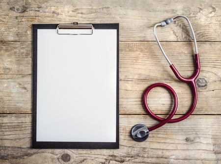 clip board: Workplace of a doctor. Stethoscope and clip board on wooden desk background.