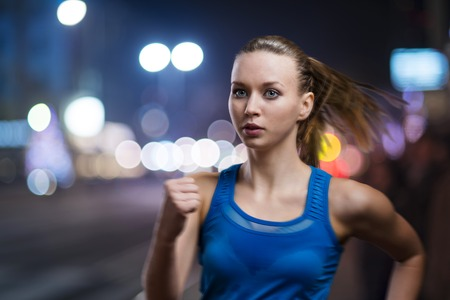 white singlet: Young woman jogging at night in the city Stock Photo
