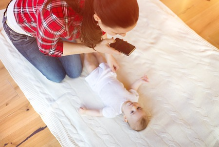 Young mother taking a picture of her cute little baby girl lying on a blanket in a living room. photo