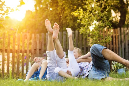 Happy young family showing legs outside in green nature. Stock Photo