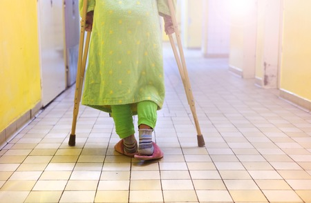 leg injury: Senior woman injured sitting in the hallway of hospital holding crutches Stock Photo
