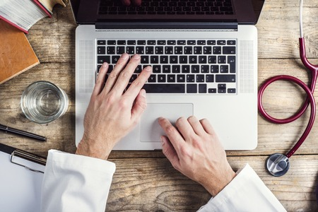 Hands of unrecognizable doctor writing on a computer. Wooden desk background. Stock Photo