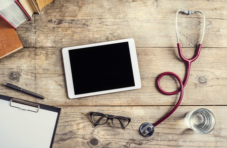 stethoscope: Workplace of a doctor. Tablet, stethoscope, clip board, books, glasses and other things on wooden desk background. Stock Photo