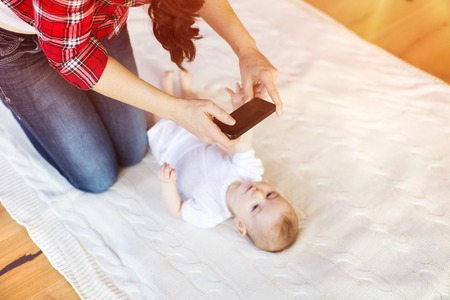 거실에서 담요에 누워 그녀의 귀여운 작은 아기 소녀의 사진을 촬영 한 젊은 어머니. 스톡 콘텐츠