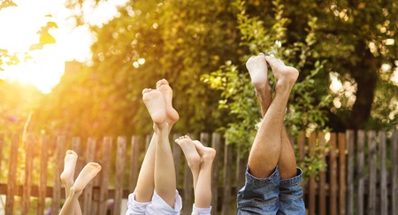 playful: Happy young family showing legs outside in green nature. Stock Photo