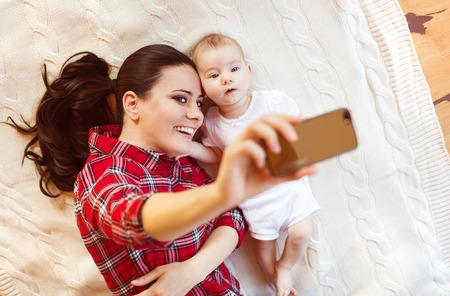Cute little baby girl and her mother taking selfie on a blanket in a living room. Stock Photo