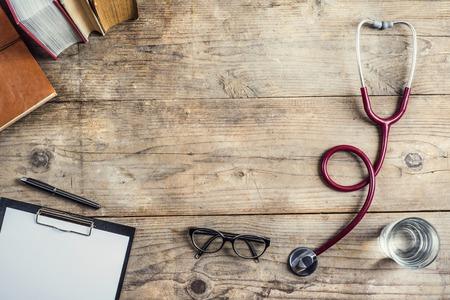 의사의 직장입니다. 청진 기, 클립 보드, 나무 책상 배경에 책, 안경과 다른 것.