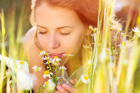 Attractive young woman with flowers outside on a meadow. Stock Photo