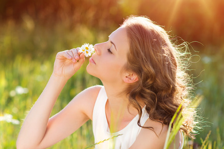 sunlit: Attractive young woman with flowers outside on a meadow. Stock Photo