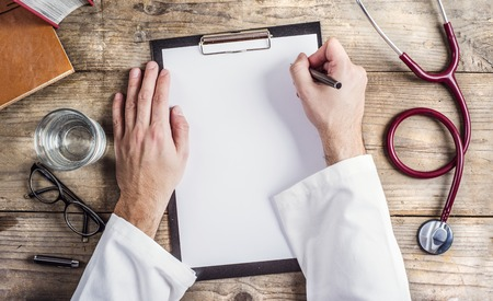 doctor writing: Hands of unrecognizable doctor writing on a blank sheet of paper. Wooden desk background.