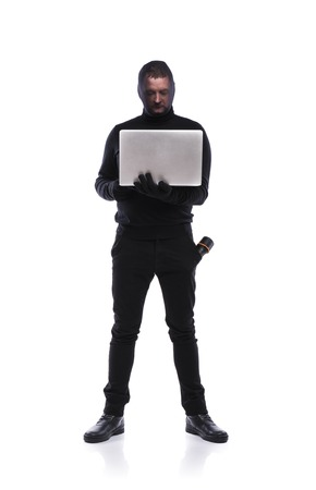 breaking the code: Thief in action stealing information with balaclava on his face, dressed in black. Studio shot on white background. Stock Photo